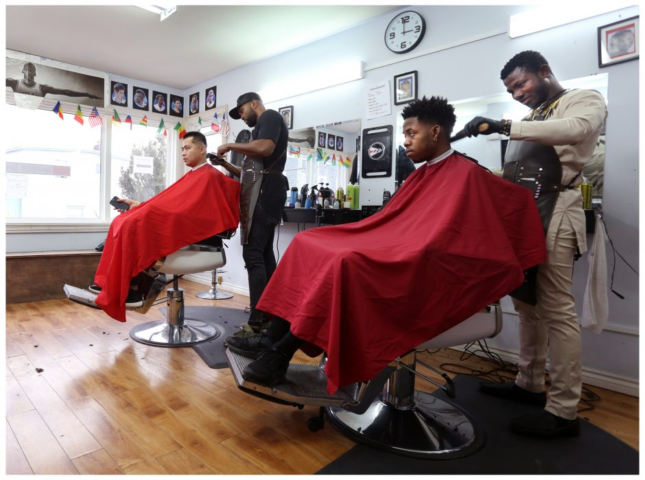 Gustavo Valoyes from Cali, Colombia, works on Jay-C who just moved to St. John's from Vancouver. Right: Yaw Antwi-Adjei from Ghana cuts the hair of Sea-Hawk Daniel Gordon.