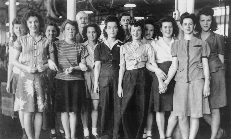 A group of employees on the factory floor of Dominion Woolens and Worsted Ltd., at some time in the 1940s. The only names documented with the photo are of the two male foremen at the back. Courtesy Hespeler Heritage Centre.