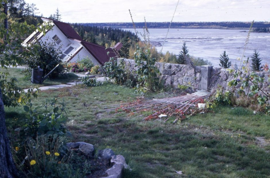 After the landslide, shifting sand carried two houses over the high riverbank and left a third teetering over the edge. (Northern Life Museum & Cultural Centre)