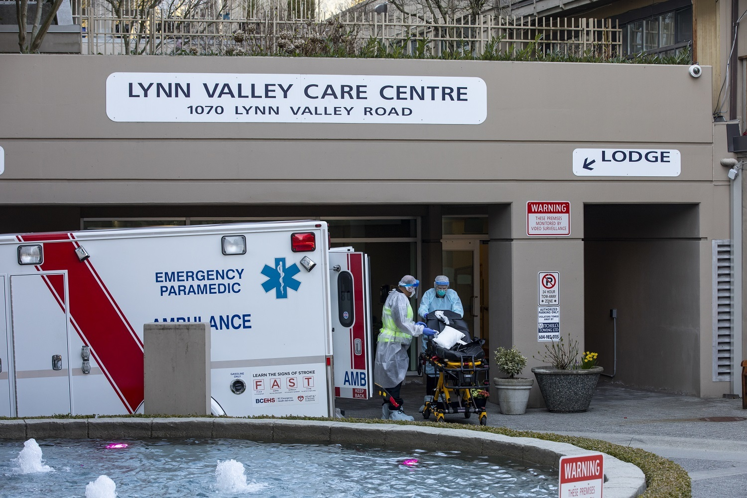 Paramedics wearing full body protective equipment clean a stretcher after responding to a call at the Lynn Valley Care Centre in North Vancouver, British Columbia on Friday, March 20, 2020. (Ben Nelms/CBC)