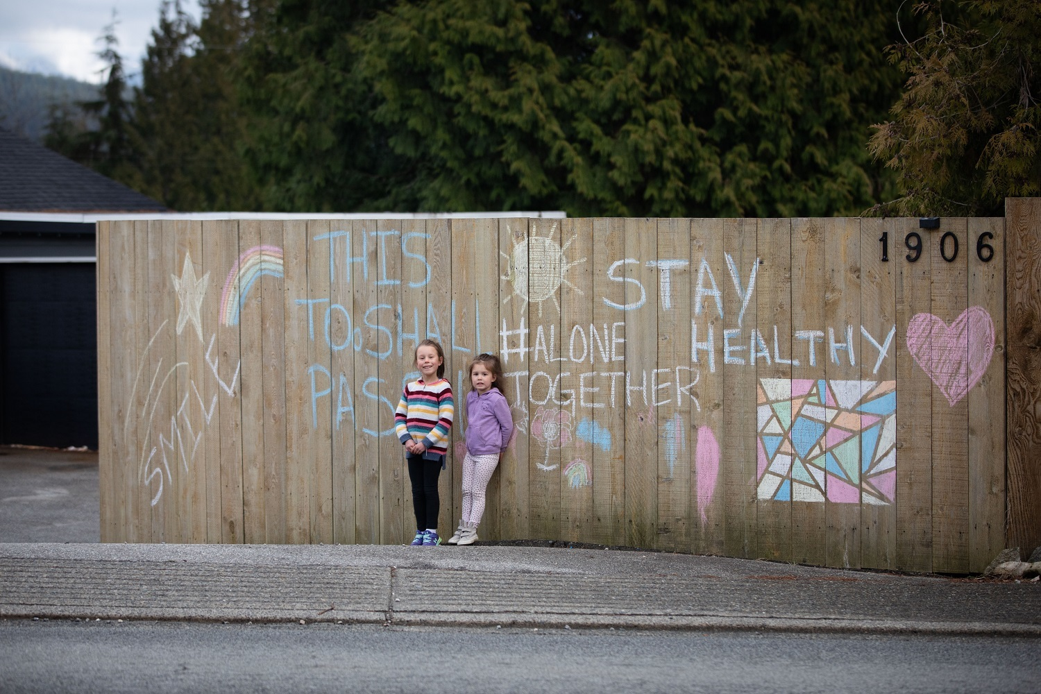 Presley Muir, 4, and Scotia Muir, 6, stand in front of a chalk sign they drew while trying to keep busy over the weekend in North Vancouver on Monday, March 23, 2020. (Maggie MacPherson/CBC)