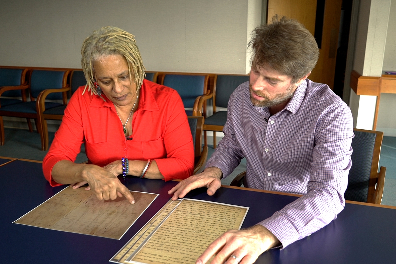 Meli Short-Colomb pores over documents related to the sale with professor Adam Rothman, who now runs the Slavery Archive at Georgetown. (Jason Burles/CBC)