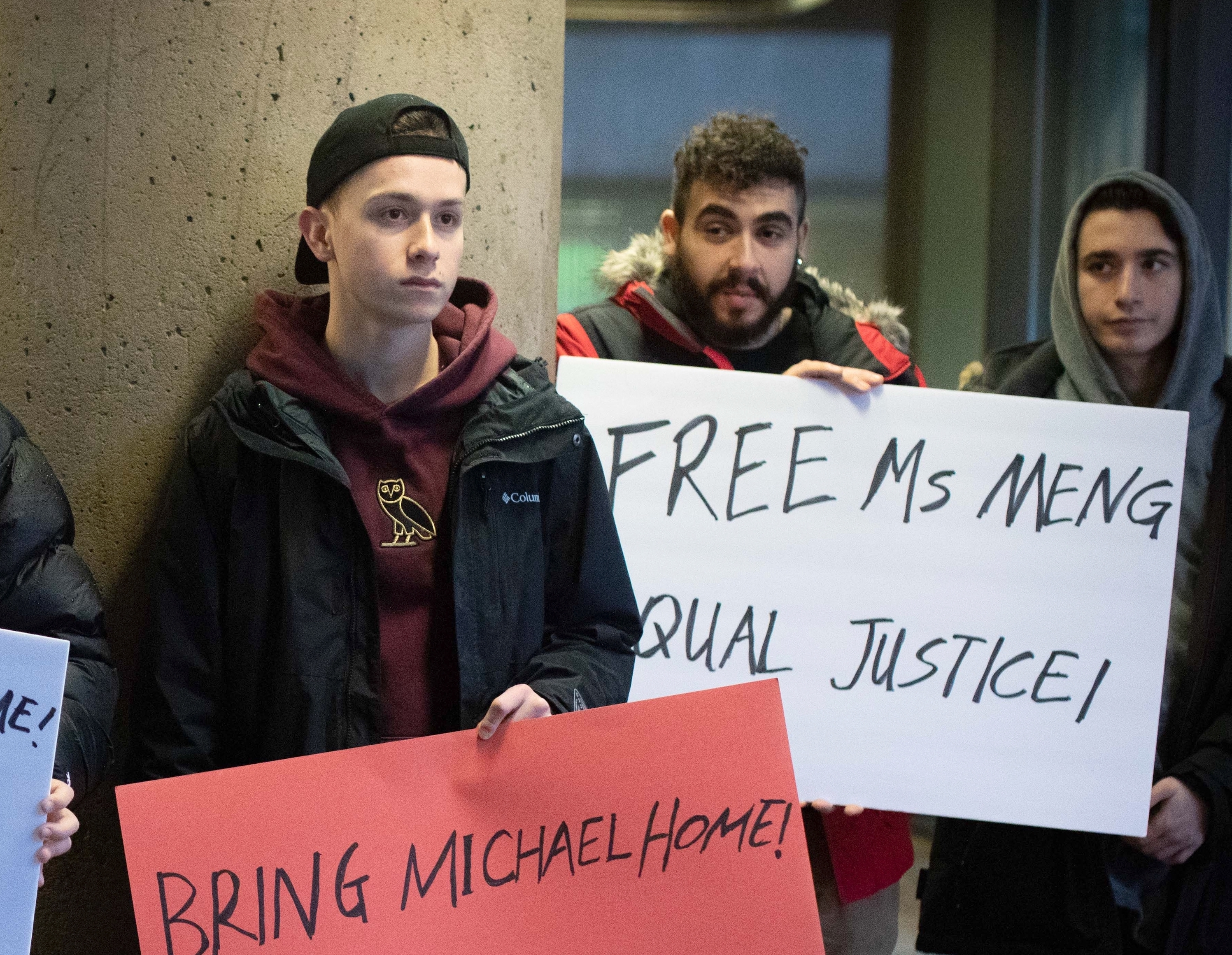 According to people paid to protest at Meng's January hearing in Vancouver, a woman named Joey provided them with the signs. (Maggie MacPherson/CBC)