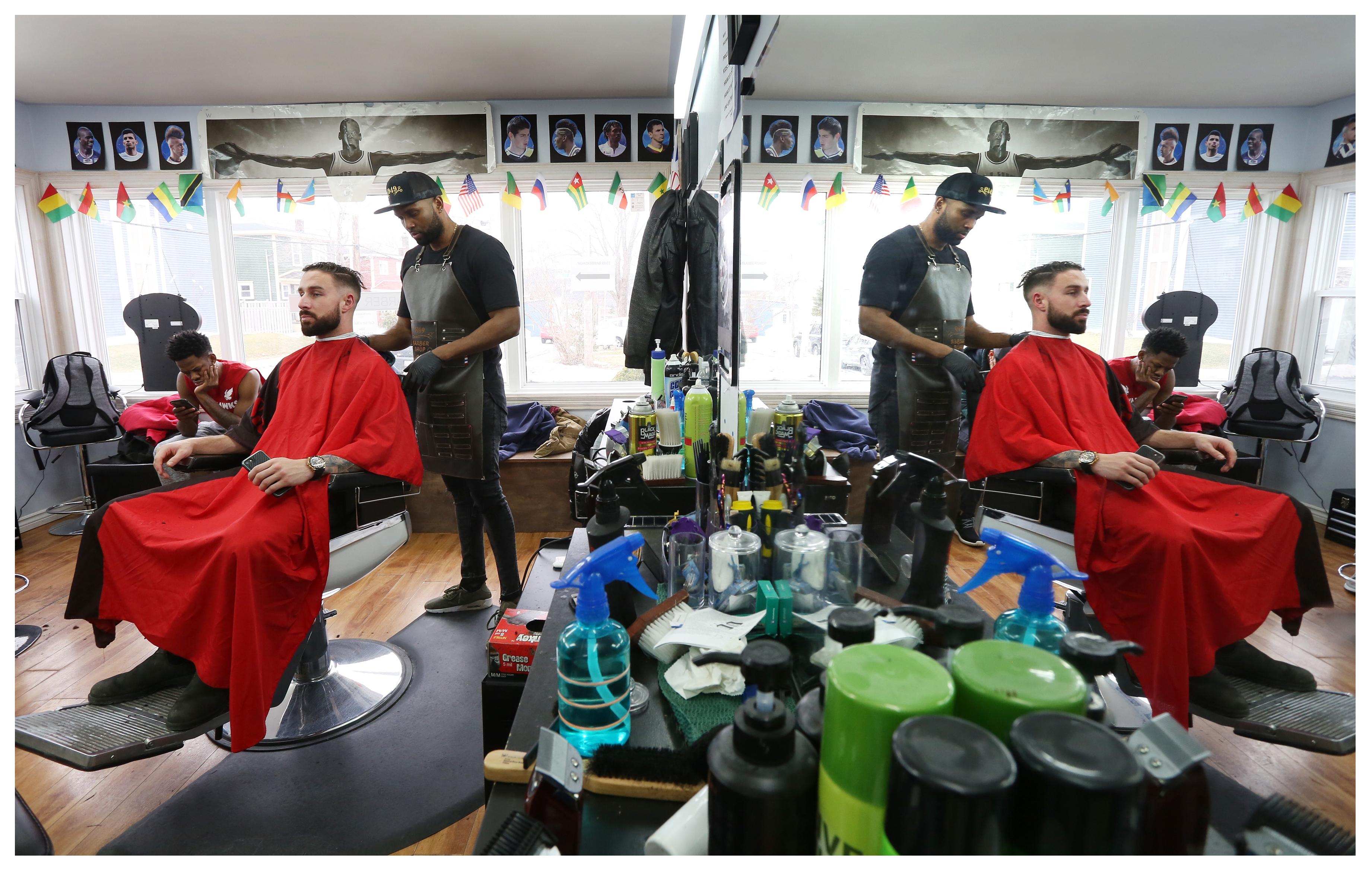 Liam Condon getsa haircut from co-owner Gustav Valoyes, as Sea-Hawk Daniel Gordon waits for his turn. (Paul Daly)