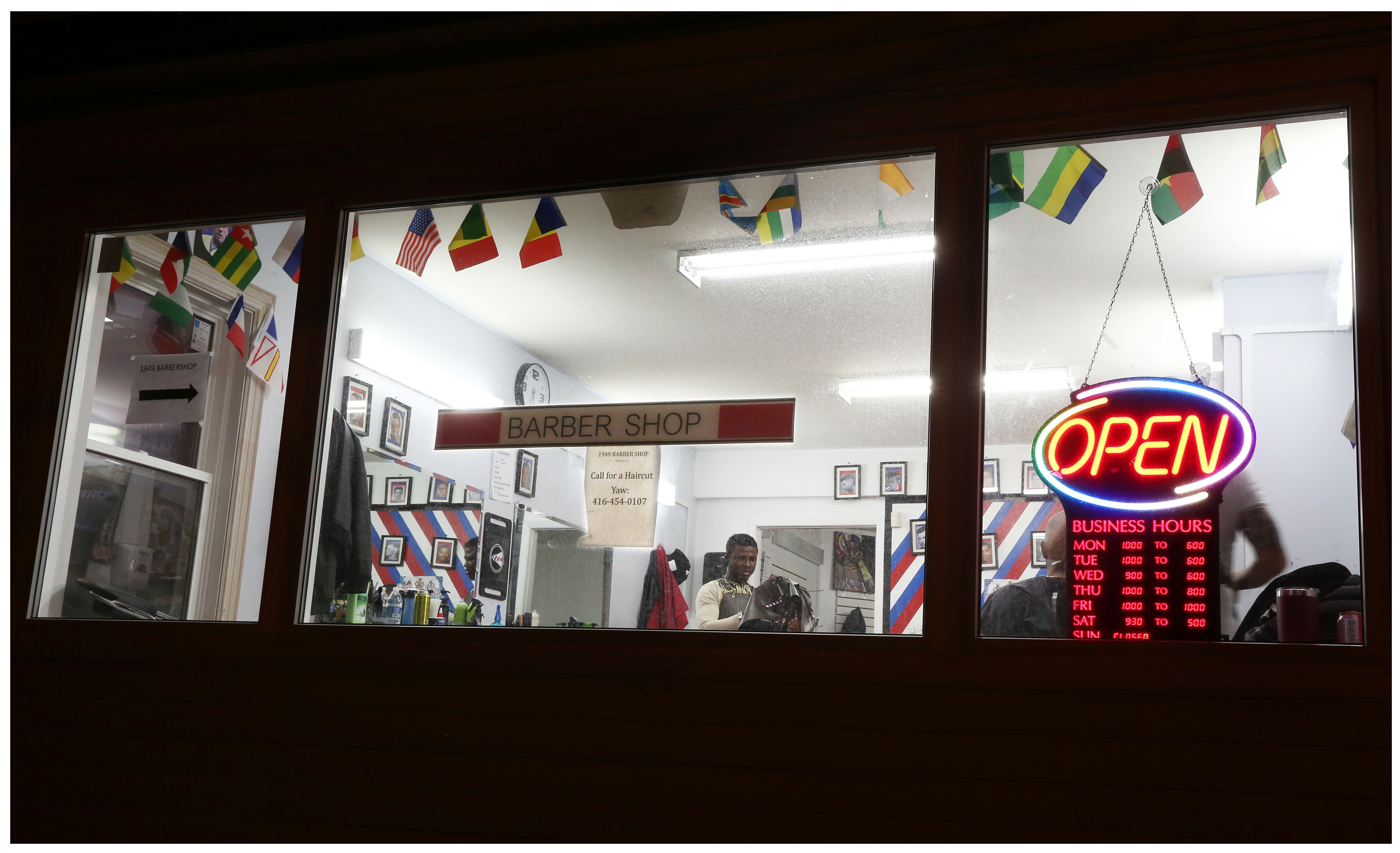 Yaw Antwi-Adjei works late one evening at 1949 Barber Shop. (Paul Daly)