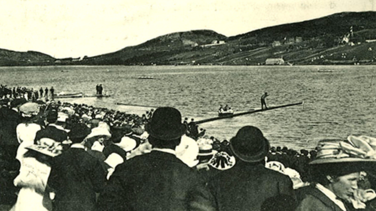 A crowd watches as someone attempts the greasy pole contest at the Regatta in the 1900s. (The Rooms)