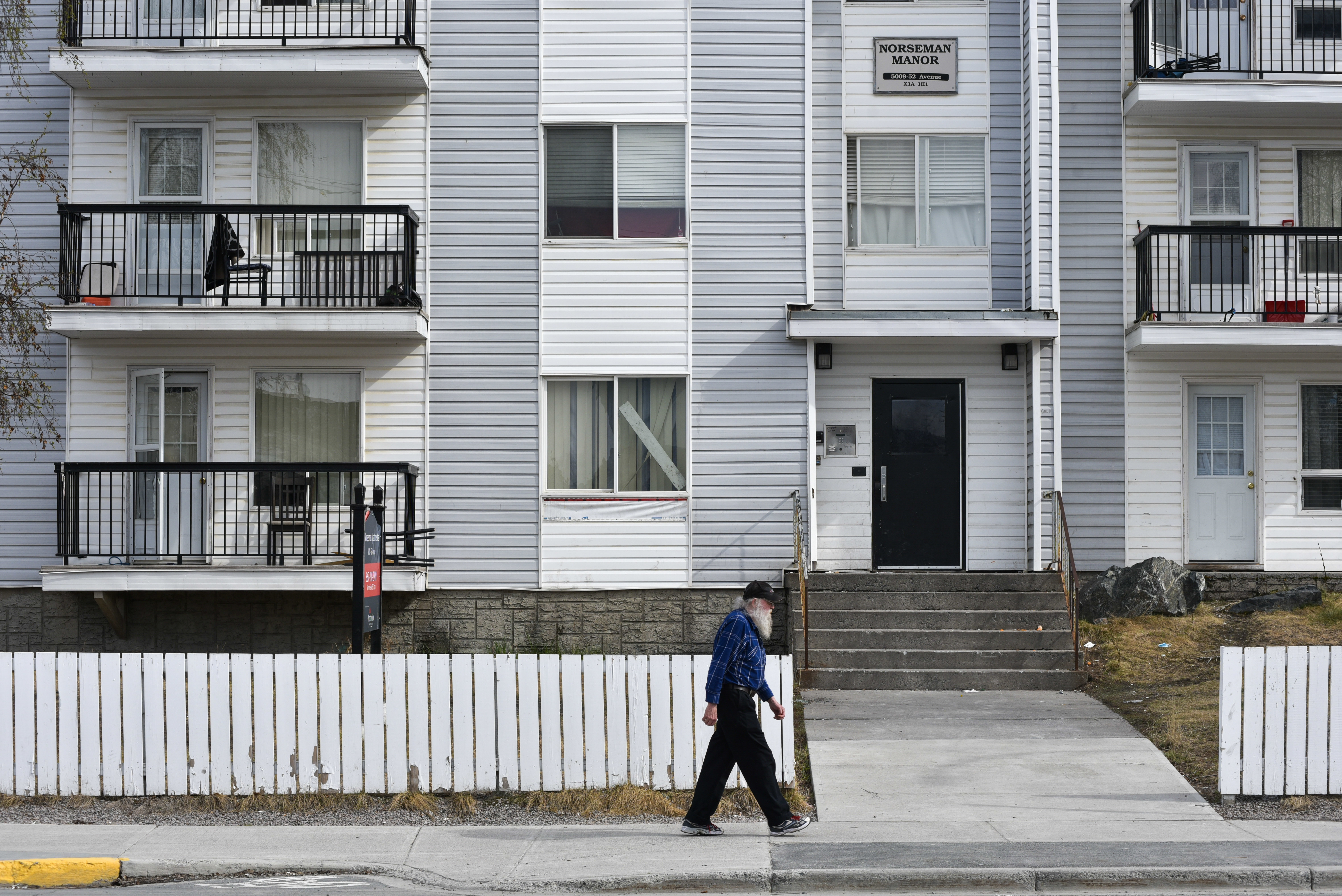 A man walks past Northview's Norseman Apartments in Yellowknife. Following the 2008 financial crisis, Northview acknowledged in its annual reporting that it had been deferring maintenance on properties for some time. (Walter Strong/CBC)