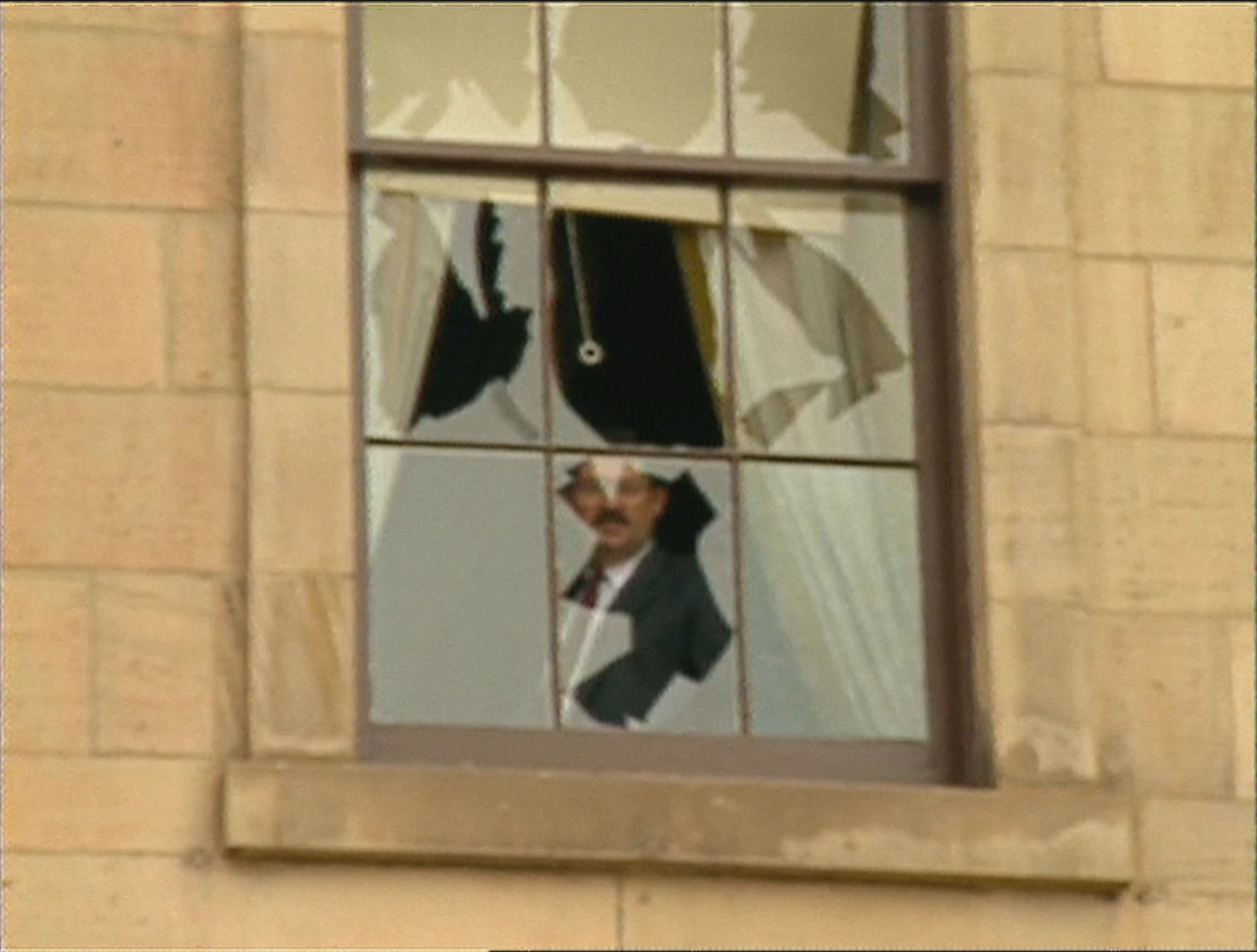 A man looks out from a shattered window at Province House. (CBC)