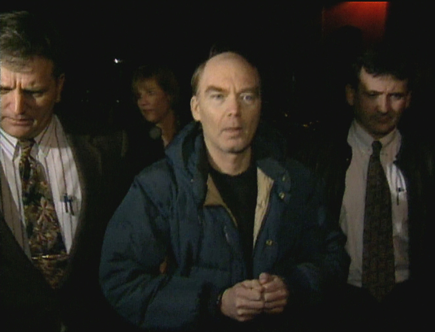 Roger Bell, flanked by Charlottetown police, after his arrest in December 1996. (CBC)