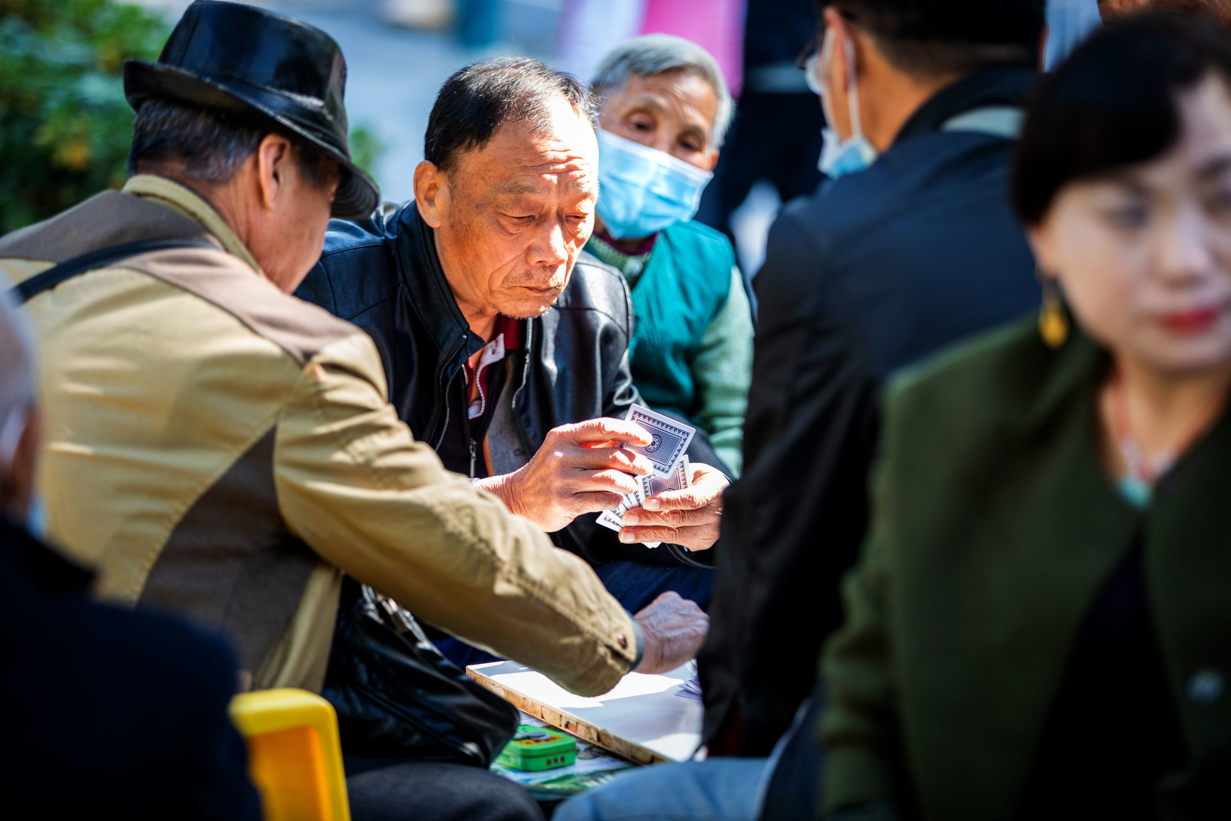 Daily life has returned to Wuhan's parks and squares, where COVID-19 seems forgotten and even masks rarely interfere with a game of cards. (Saša Petricic/CBC)