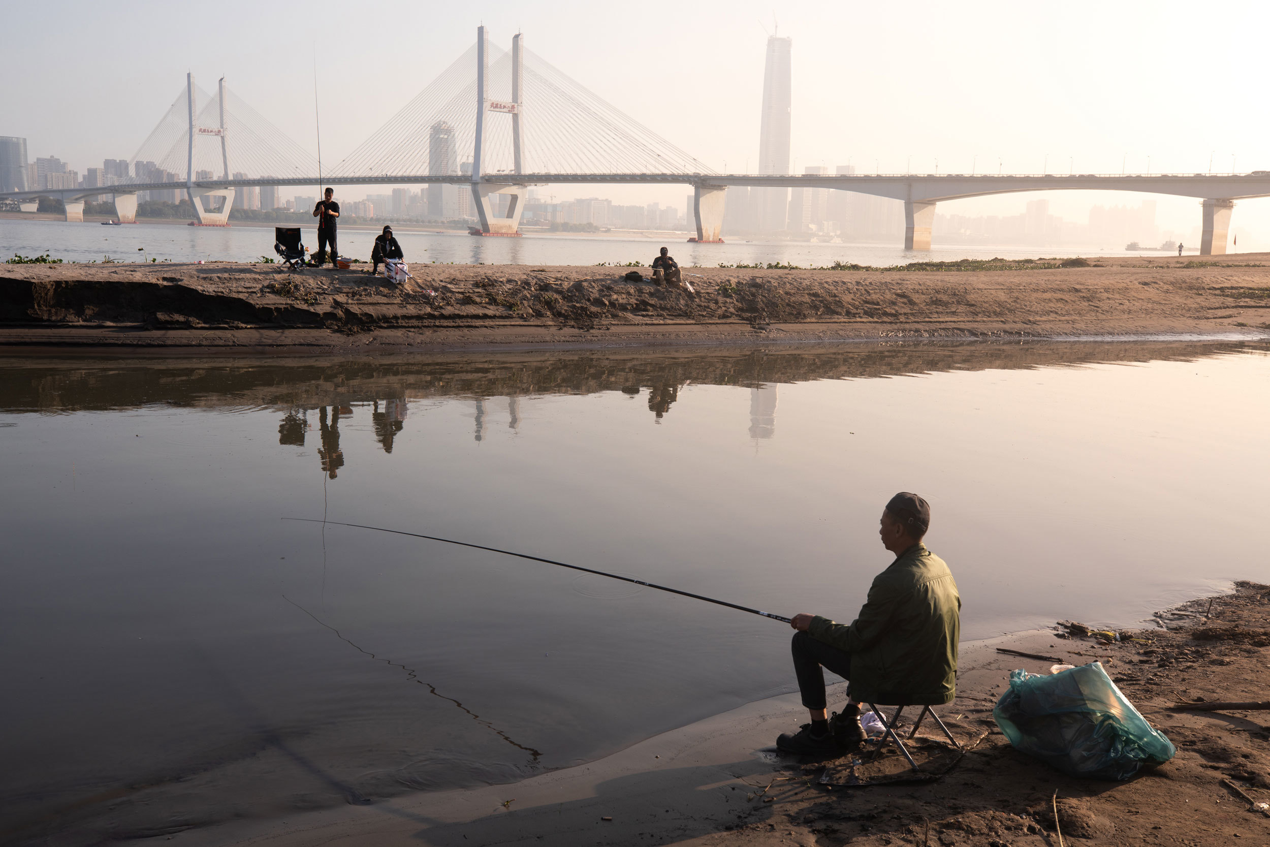 Shoppers once again crowd Wuhan's Jianghan commercial street. Meanwhile, lazy afternoons fishing on the banks of the Yangtze River have also returned. (Saša Petricic/CBC)