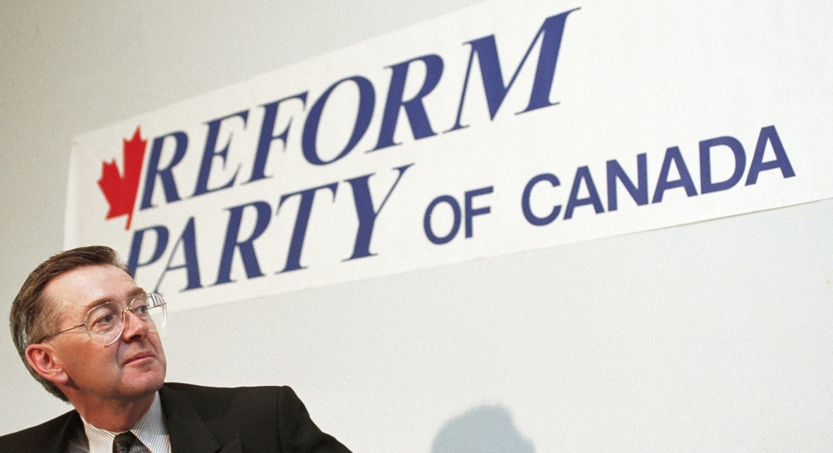 Preston Manning pauses in front of a Reform Party of Canada sign during a news conference in Ottawa on Nov. 27, 1991. (Ron Poling/The Canadian Press)