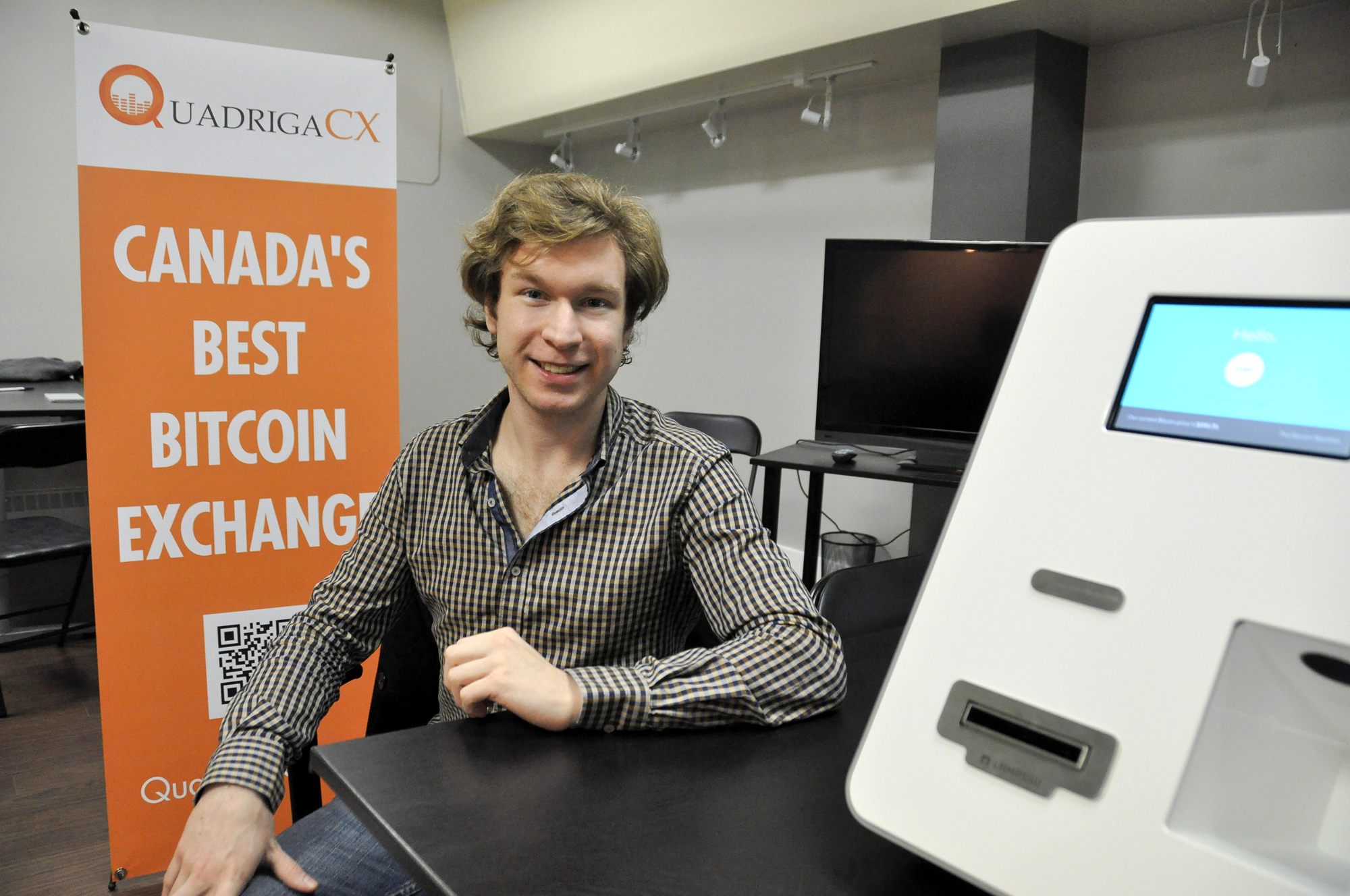 Cotten poses for a local newspaper a month after launching QuadrigaCX in 2014. He's sitting next to his first bitcoin ATM machine, located at his office in Vancouver's Gastown. (Stephen Hui/The Georgia Straight)