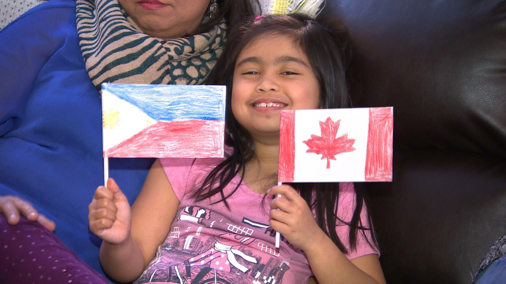 Lexie holds up two handmade flags — one for Canada and one for the Philippines. She said her dad helped her draw the maple leaf. (Travis Golby/CBC)