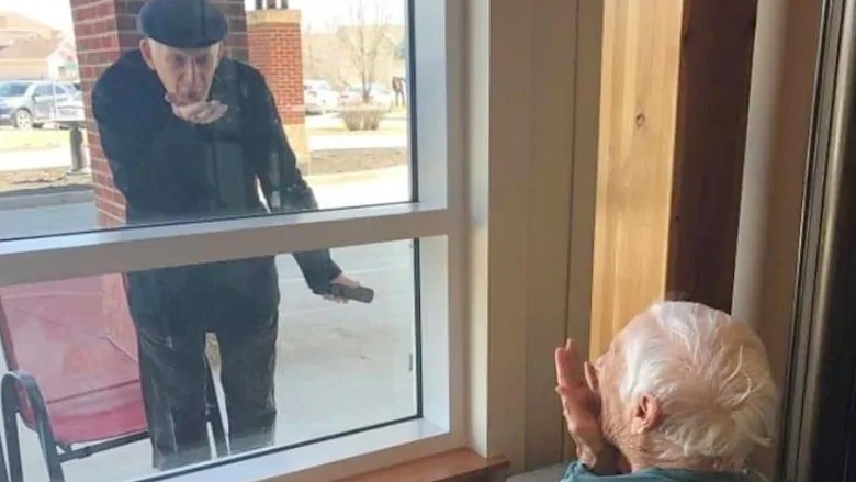 Sam Kleiman blows a kiss to his wife, Shirley, during one of the couple's daily visits at the window of Shirley's personal care home. (Submitted by the Saul and Claribel Simkin Centre)