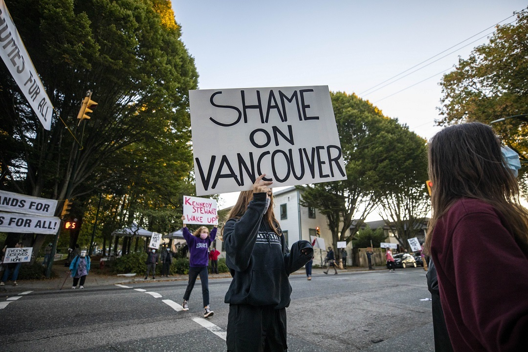 """Demonstrators hold signs near Strathcona park calling for safe housing of homeless people camped in the park in Vancouver in September. Pete Fry, city councillor, says a sort of """"protest leadership"""" at the encampment has made it challenging for outreach workers to connect with campers. (Ben Nelms)"""