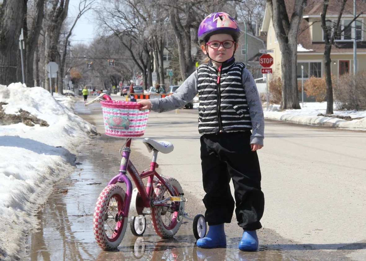 Sia Roberts took her bike down Wolseley Avenue, which was closed to cars, in April. Sia's nursery school was also closed due to COVID-19. (Ian Froese/CBC)