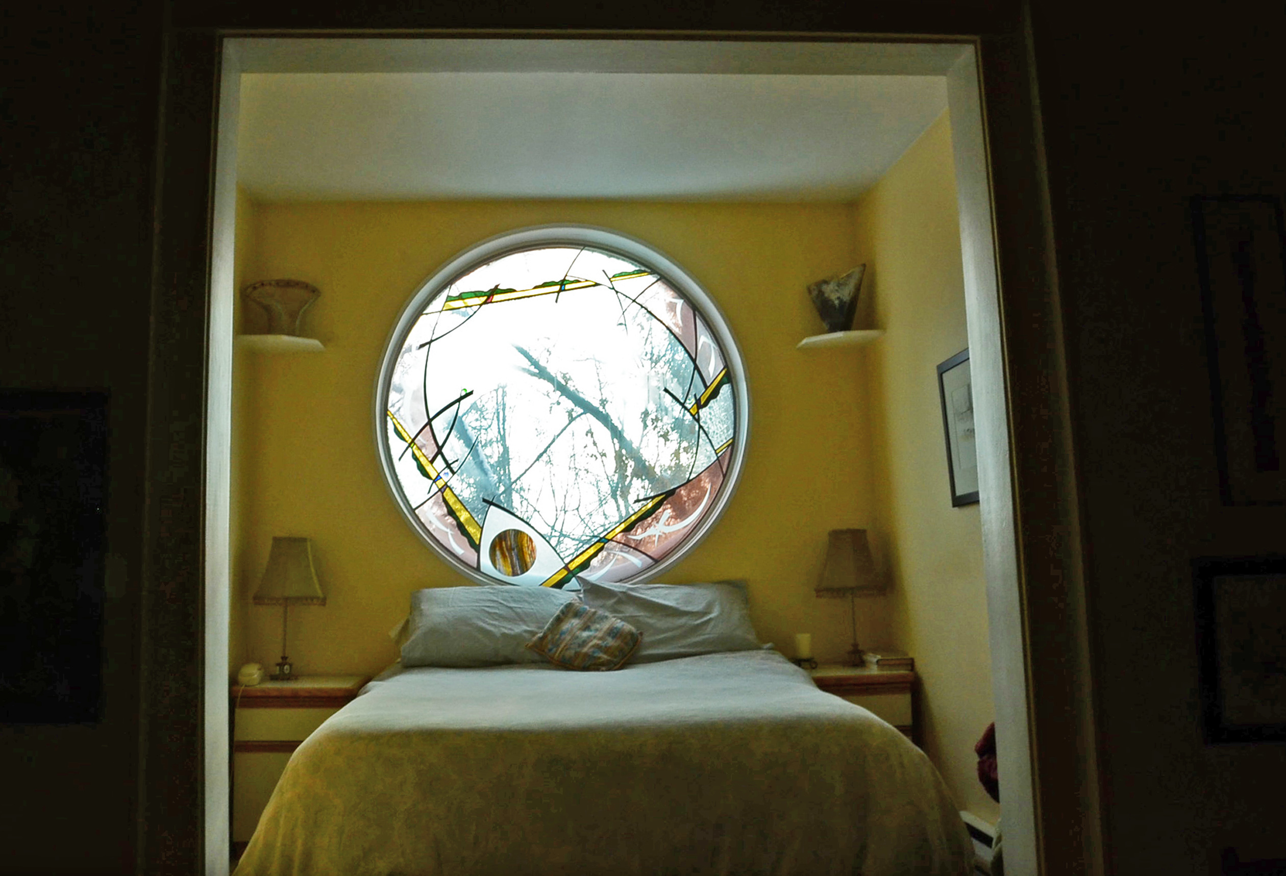 The master bedroom of Holden and Bolen's home is outfitted with a custom stained glass window. (Bridget Yard/CBC)