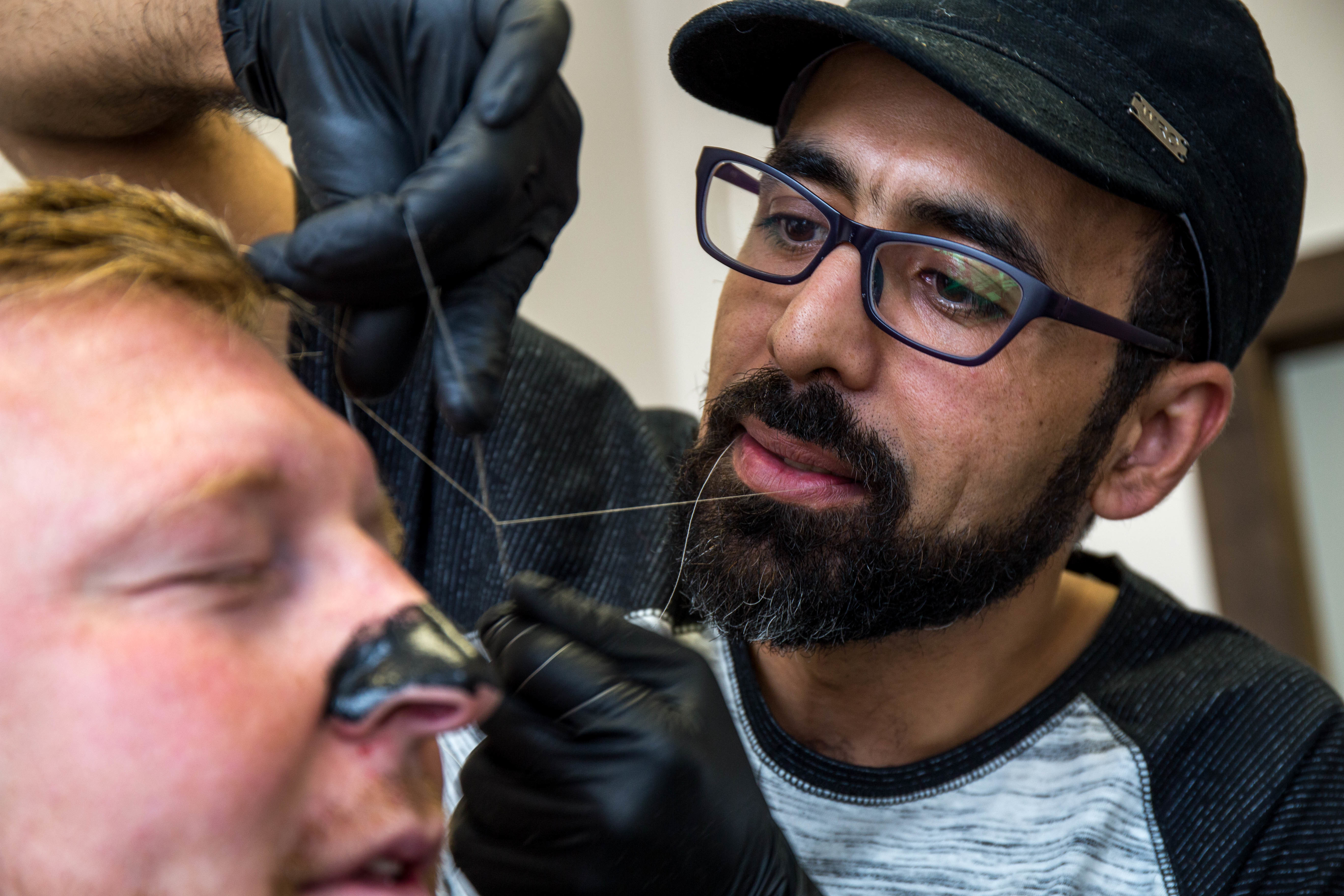 Mohamad Almaidani uses' old school' techniques, including thread and razors, to give his customers a polished look. (Lindsay Bird/CBC)
