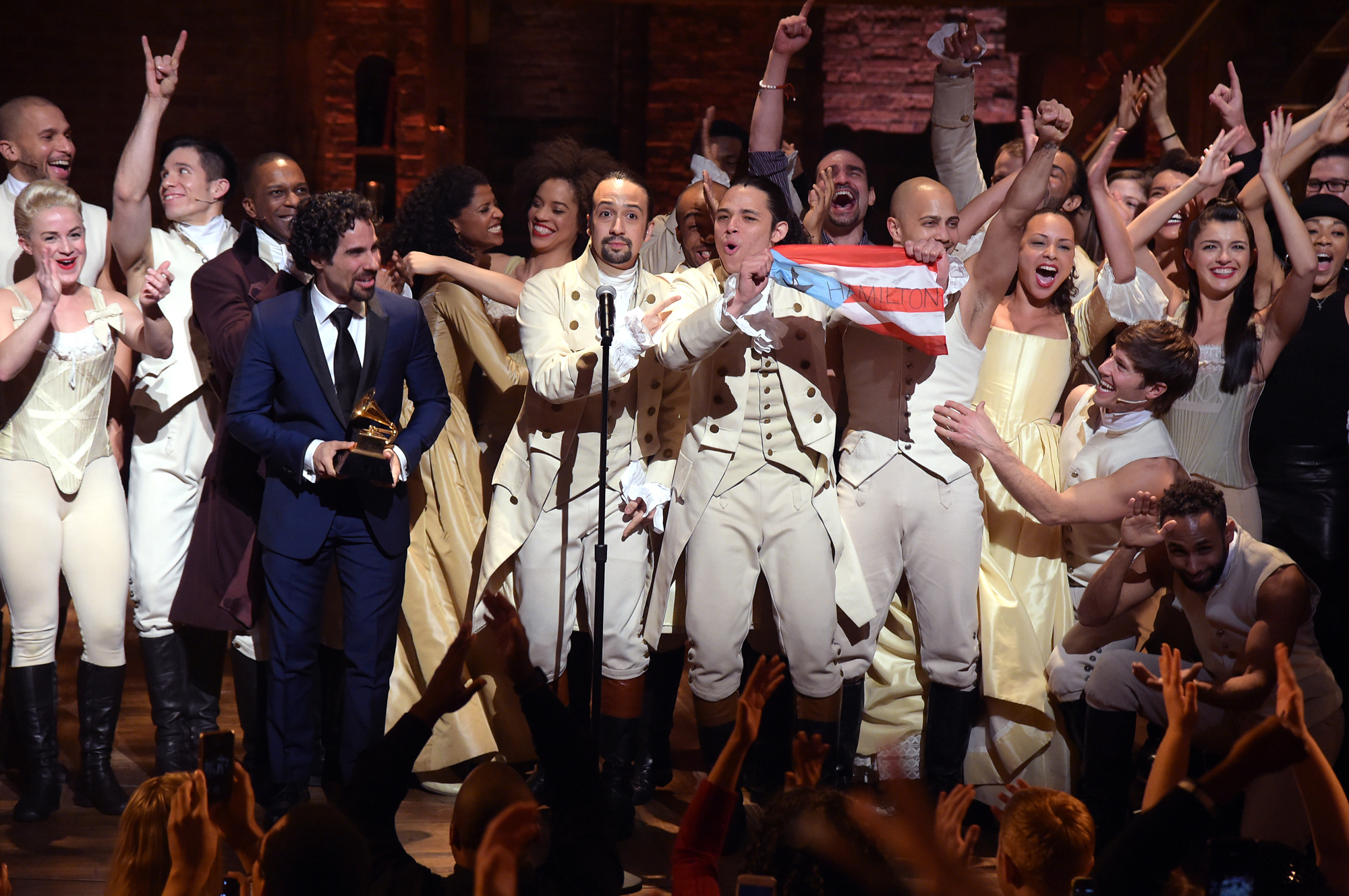 Cast and crew of Hamilton, including composer Lin-Manuel Miranda, at the microphone, celebrate on stage during a performance at the Grammy Awards on Feb. 15, 2016, in New York. (Theo Wargo/Getty Images)
